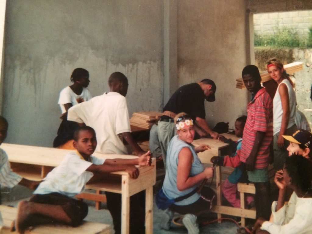 Becca (center) and Luke (leaning next to Becca) building a desk for a school at AFCA Village.