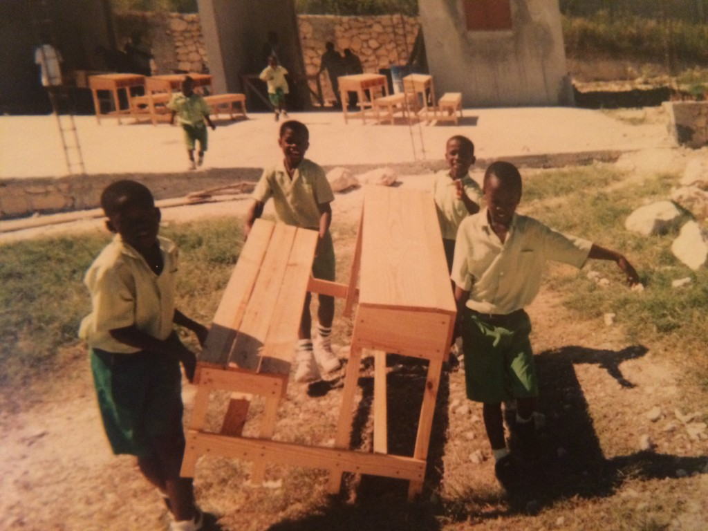 Students carry a finished desk to their classroom at AFCA village.